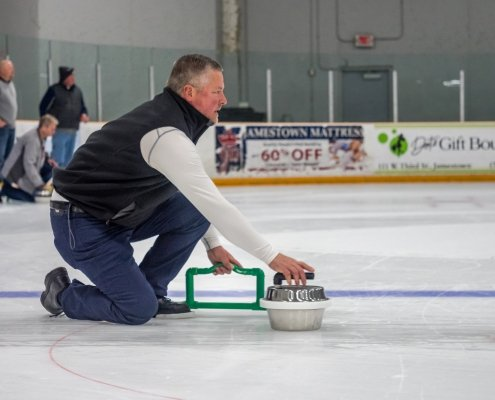 A man prepares to push his backyard curling stone down the ice.