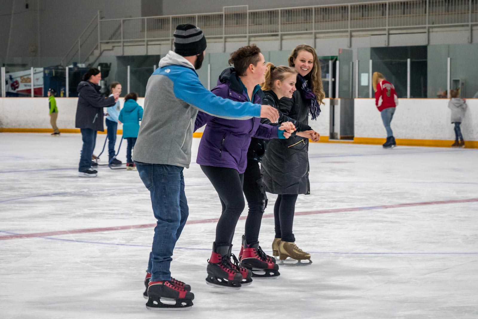 Four friends ice skate while holding hands and smiling