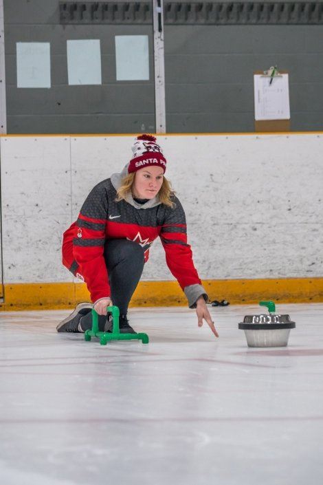 A woman pushes a backyard curling stone down the ice