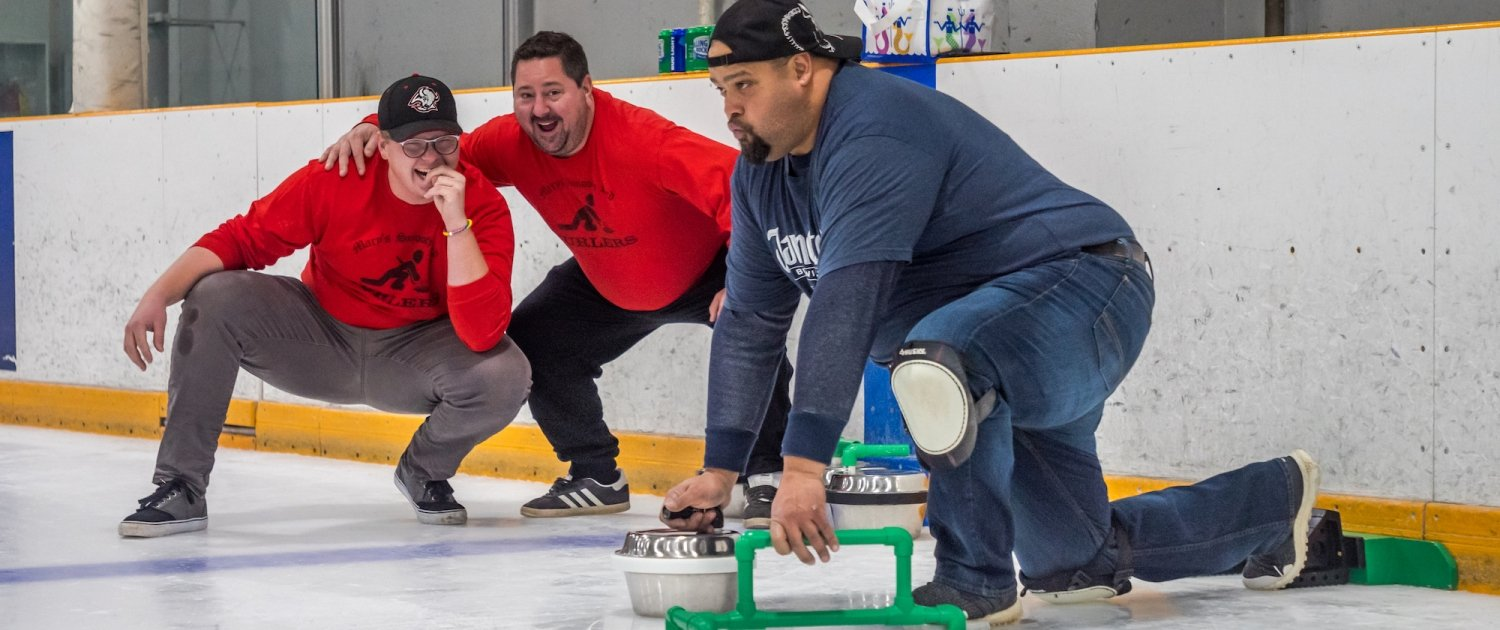 Two teammates watch on as their rival prepares to push his backyard curling stone down the ice.