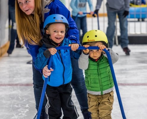 A mom helps her two boy children ice skating with a skating trainer
