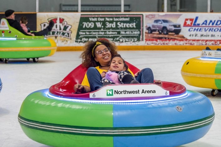 A women and child smile and look like they are having fun in Northwest Arena's Ice Bumper Car