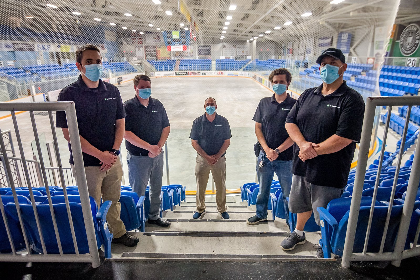 Staff at the Northwest Arena posing on the stairs of ice Rink A, wearing masks