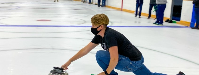 A woman pushes a Backyard Curling Stone down the ice while other players stand in the background. Everyone is wearing face masks.
