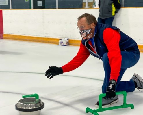 A man pushes a Backyard Curling stone while his teammate watches. They are both wearing face masks.