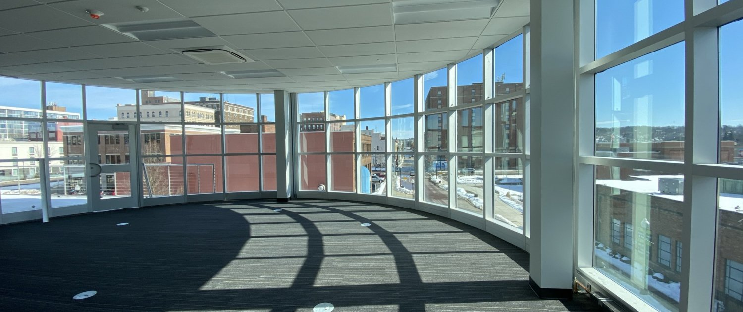Preview of a new meeting and event space with lots of windows and a city backdrop