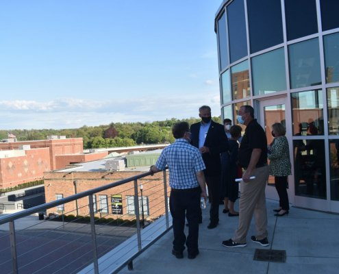 People stand on a rooftop patio at the Northwest Arena. The view is of downtown Jamestown.