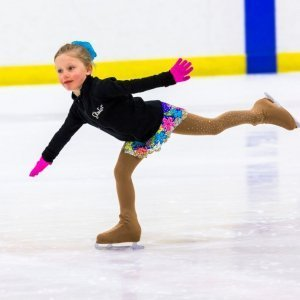 A young girl is balancing on one leg while ice skating with arms outstretched