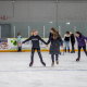 Two groups of friends are skating while holding hands. More skaters are in the background.