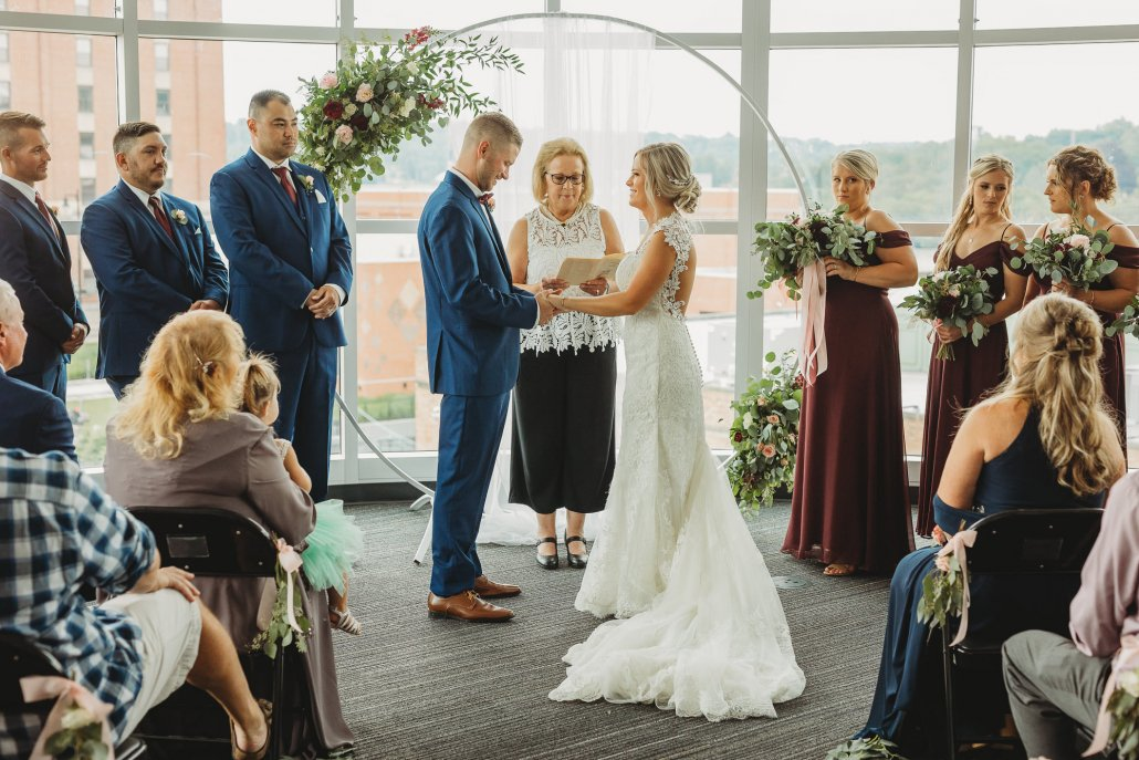 a bride and groom exchange vows at the altar