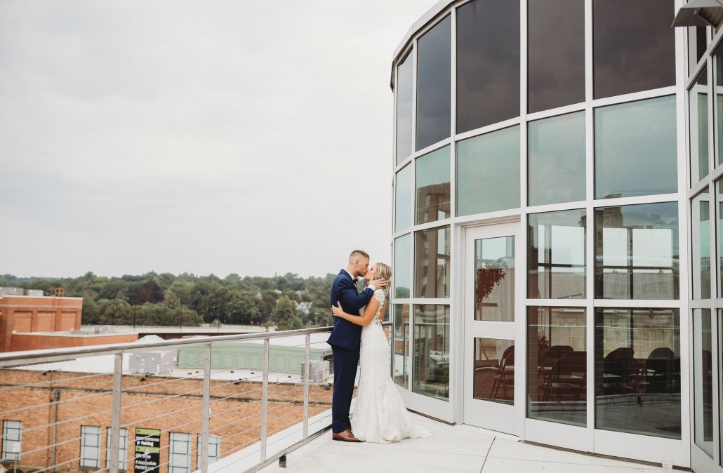 bride and groom pose for a portrait on the Atrium Rooftop Patio
